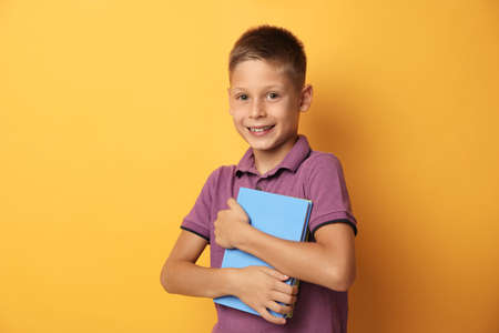 Portrait of cute little boy with books on yellow background. Reading concept