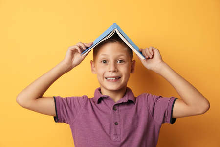Portrait of cute boy with book on yellow background. Reading concept