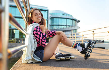 Beautiful young woman with roller skates sitting outdoors