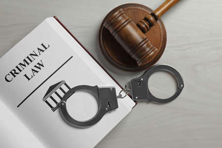 Judge's gavel, handcuffs and Criminal law book on white wooden background, flat lay