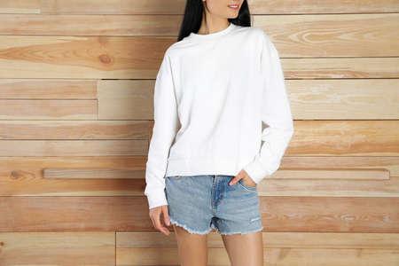 Jeune femme en pull au mur en bois, gros plan. Maquette pour la conception