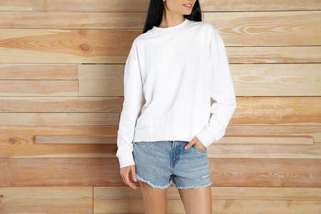 Young woman in sweater at wooden wall, closeup. Mock up for design