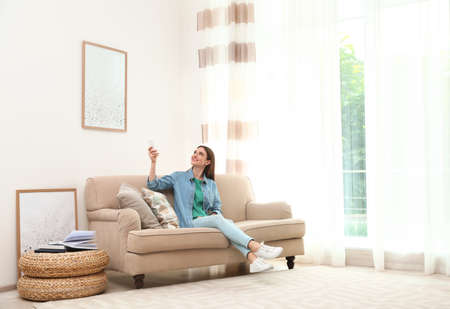 Happy young woman switching on air conditioner with remote control at home