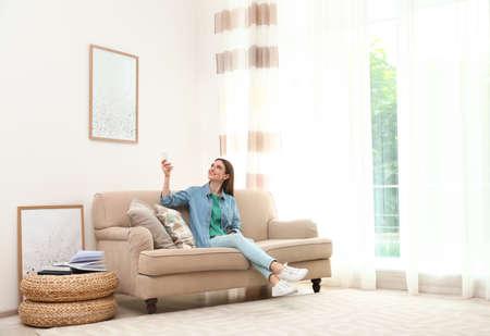 Mujer joven feliz encender el aire acondicionado con control remoto en casa Foto de archivo