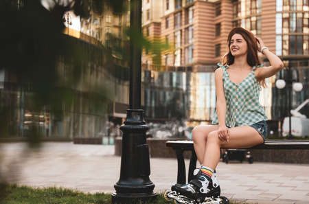 Beautiful young woman with roller skates sitting on bench outdoors, space for text 版權商用圖片