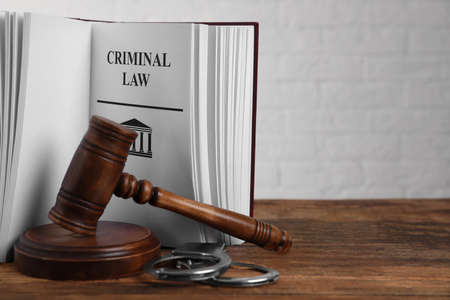 Book with words CRIMINAL LAW, handcuffs and gavel on wooden table. Space for text Zdjęcie Seryjne