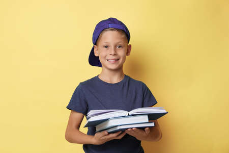 Portrait of cute little boy reading book on yellow background