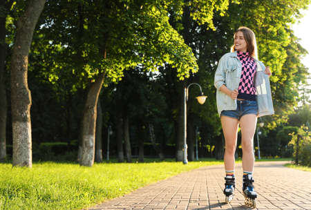Beautiful young woman with roller skates having fun outdoors, space for text 版權商用圖片