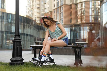 Beautiful young woman putting on roller skates outdoors
