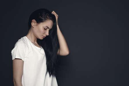 Porträt der verärgerten jungen Frau auf dunklem Hintergrund. Platz für Text Standard-Bild