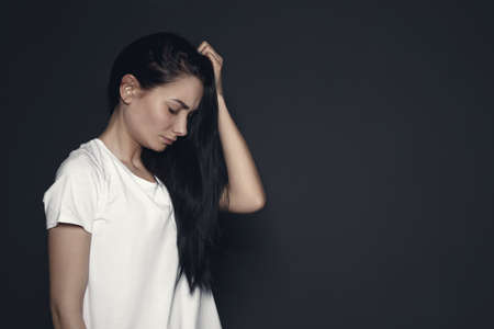 Portrait of upset young woman on dark background. Space for text Standard-Bild