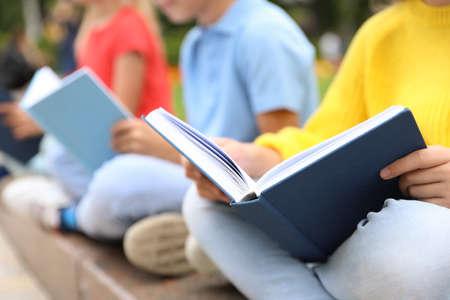 Little children reading books outdoors, closeup