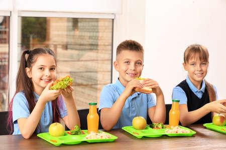 Niños felices en la mesa con comida sana en el comedor escolar Foto de archivo