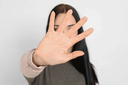 Young woman making stop gesture against white background, focus on hand