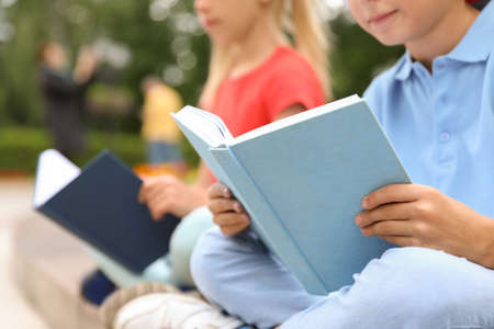 Little children reading books outdoors, closeup