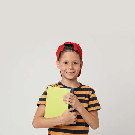 Portrait of cute little boy with books on grey background. Reading concept Reklamní fotografie