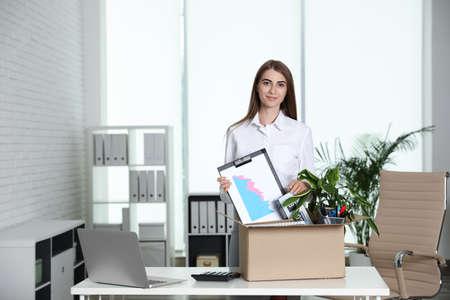 Heureuse jeune femme emballant des trucs dans une boîte au bureau