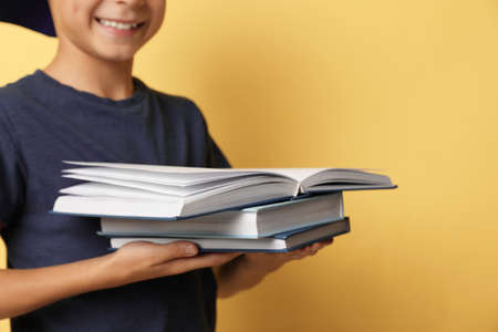 Little boy reading book on yellow background, closeup