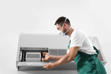 Professional male technician repairing air conditioner indoors