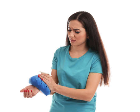 Woman with cold compress suffering from wrist pain on white background