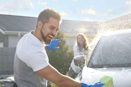 Happy couple washing car and having fun at backyard on sunny day
