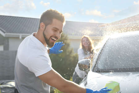 Happy couple washing car and having fun at backyard on sunny day Banco de Imagens - 134105753