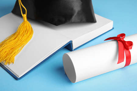 Graduation hat, open book and student's diploma on light blue background, closeup 写真素材