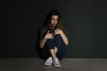 Jeune femme bouleversée assise sur le sol près du mur gris