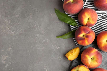 Fresh tasty peaches, fabric and leaves on grey stone surface, top view with space for text