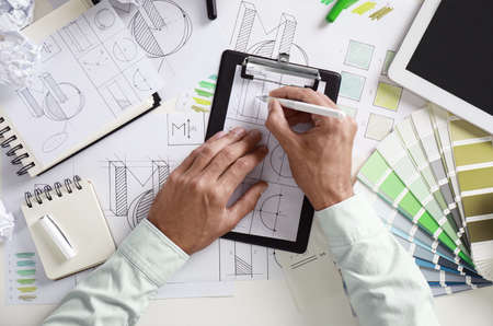 Male designer working at white table, top view
