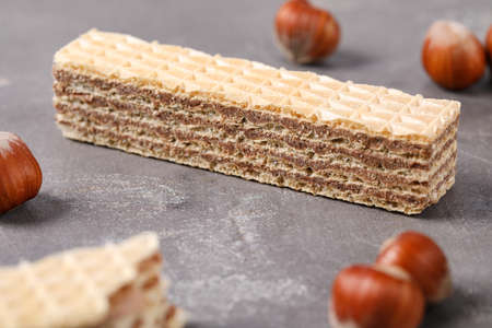 Delicious wafers with hazelnuts on grey stone background Foto de archivo