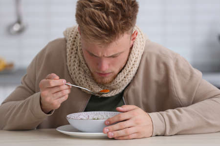 Sick young man eating soup to cure flu at table in kitchen