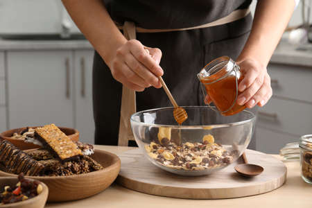 Woman preparing healthy granola bar at wooden table in kitchen