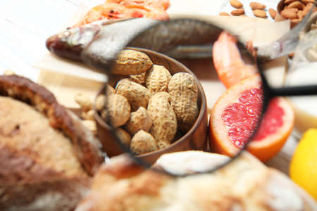 Different products with magnifier focused on peanuts and grapefruit, closeup. Food allergy concept