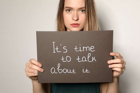 Young woman holding card with words ITS TIME TO TALK ABOUT IT against light background