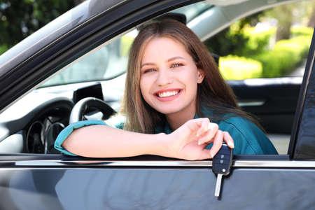 Mooie vrouw met autosleutel zittend in nieuwe auto buitenshuis
