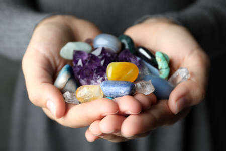 Woman holding pile of different gemstones, closeup