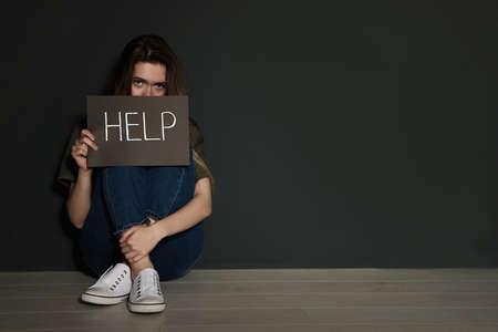 Jeune femme tenant une carte avec le mot HELP alors qu'elle était assise près d'un mur gris. Espace pour le texte