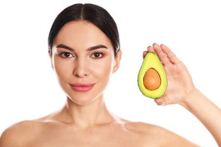 Jonge vrouw met zijdeachtige huid na gezichtsmasker die avocado op witte achtergrond houdt