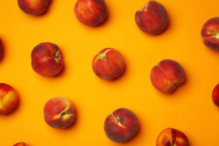 Flat lay composition with ripe peaches on orange background