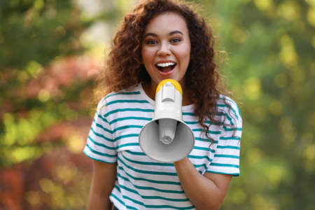 Happy African-American woman with megaphone outdoors. Meeting leader Stok Fotoğraf