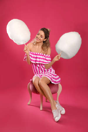 Full length portrait of young woman with tasty cotton candy sitting on pouf, pink background