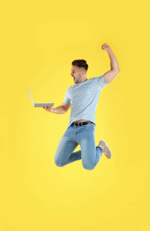 Emotional man with laptop jumping on yellow background Stok Fotoğraf