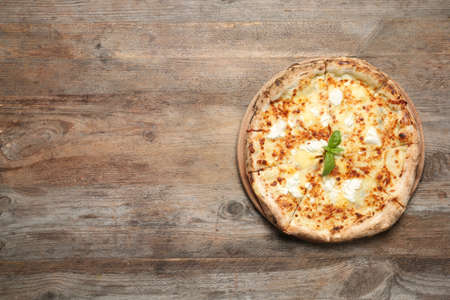 Delicious pizza with cheese and basil on wooden background, top view. Space for text Zdjęcie Seryjne - 133306147