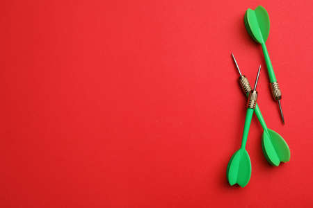 Green dart arrows on red background, flat lay with space for text Stock Photo