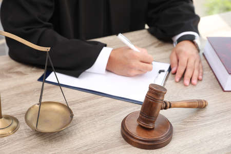 Judge working at wooden table indoors, closeup. Criminal law