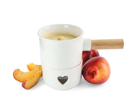 Pot with chocolate fondue and peaches on white background