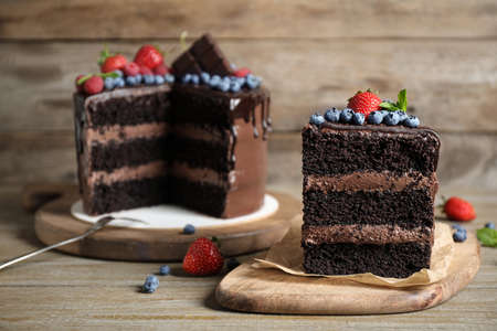 Delicious chocolate cake decorated with fresh berries on wooden table