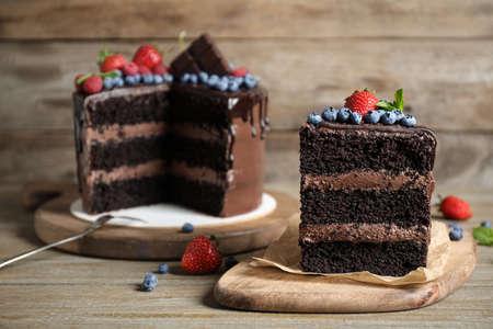 Deliziosa torta al cioccolato decorata con frutti di bosco freschi su un tavolo di legno