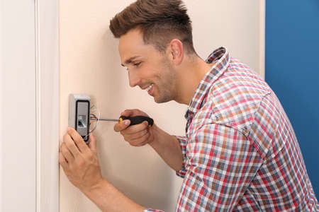 Young man installing fingerprint security alarm system indoors